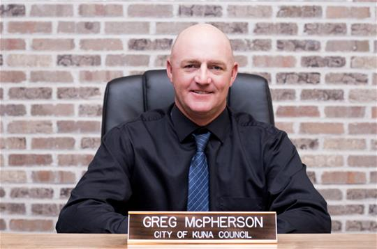Greg McPherson sitting behind nameplate in council chambers