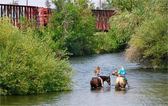 Two women on horseback in creek