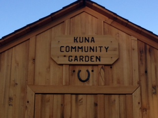 Wooden building with Kuna Community Garden sign above door