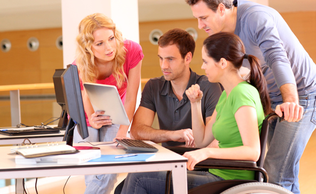 People talking around a computer