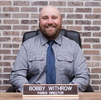 Bobby Withrow in uniform smiling sitting behind name plate at desk